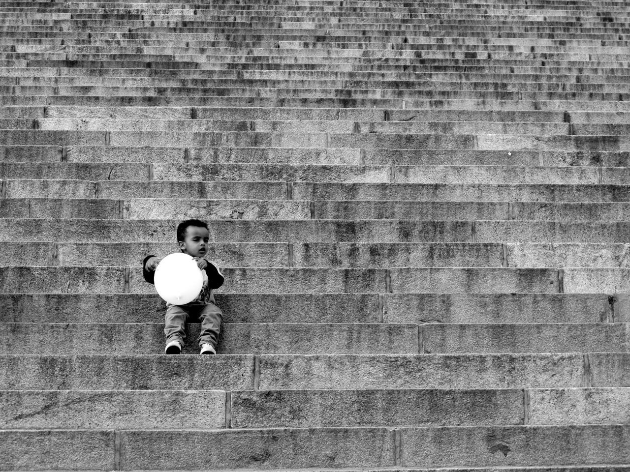 Ein Kind spielt auf den Stufen vor dem Dom mit einem Luftballon.