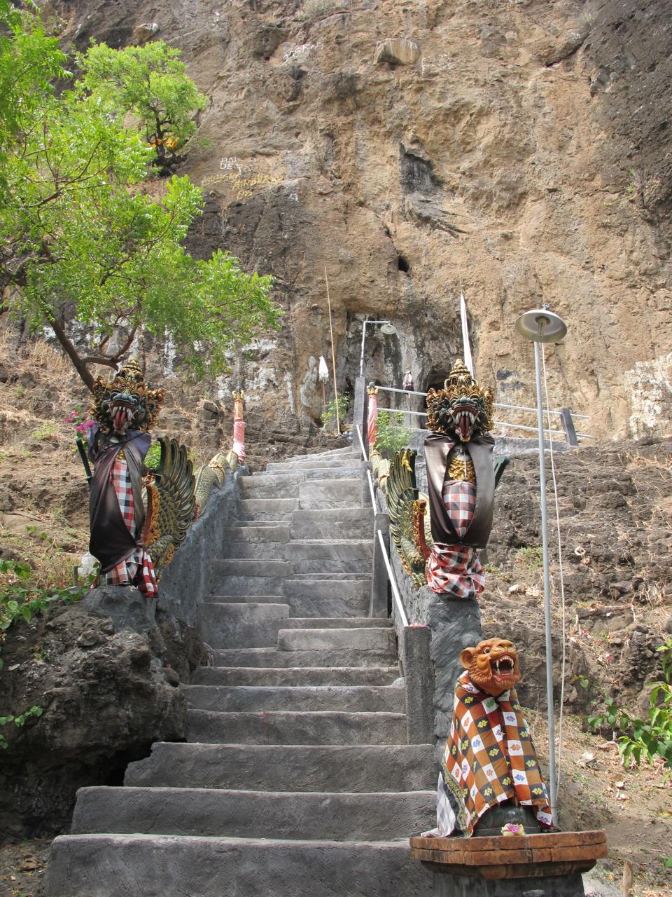 Eine schlanke Treppe führt hinauf in einen Felsentempel an der Westküste Balis.