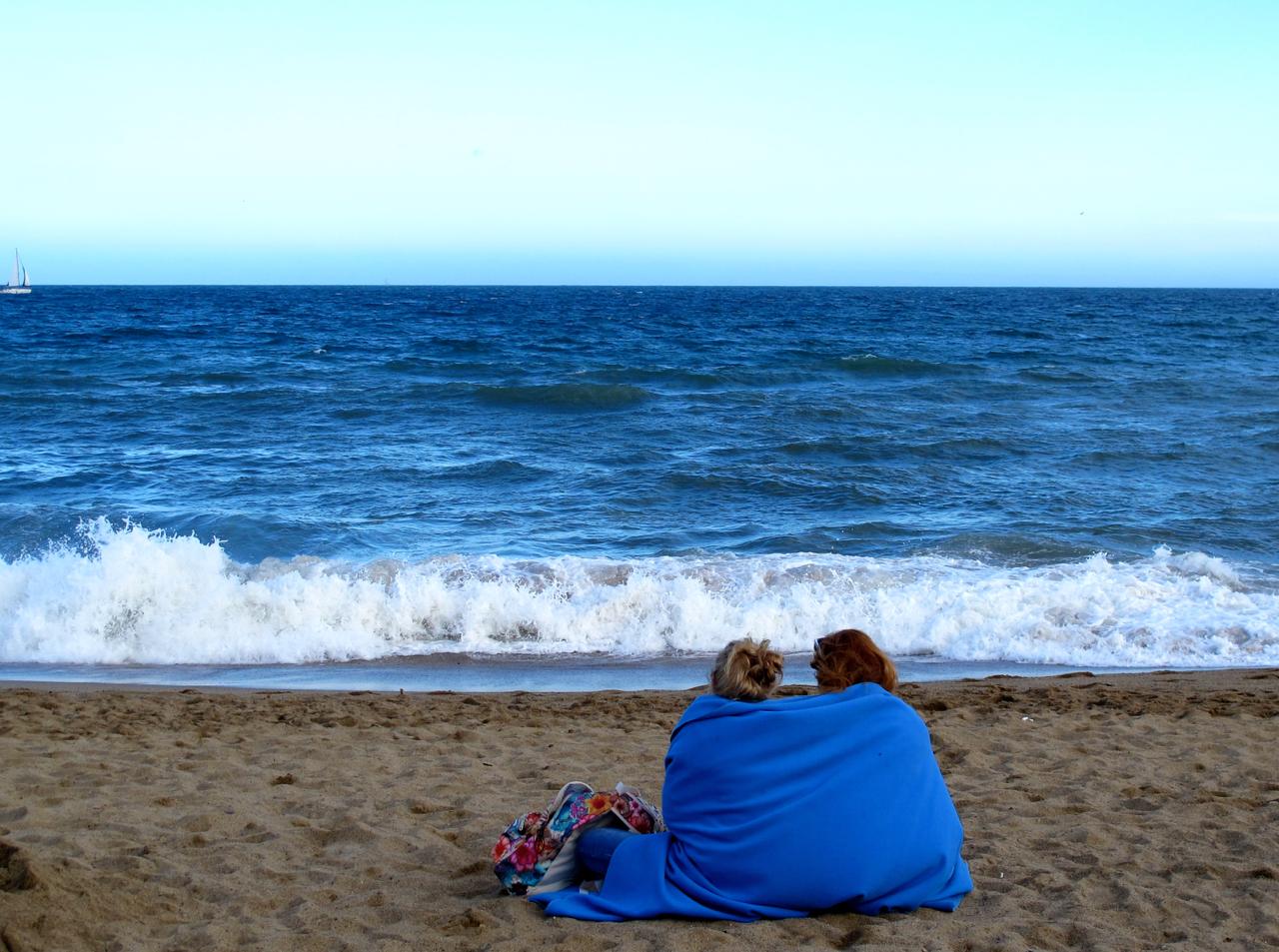 Ein Paar wickelt sich in eine Decke ein am Strand von Barcelona.