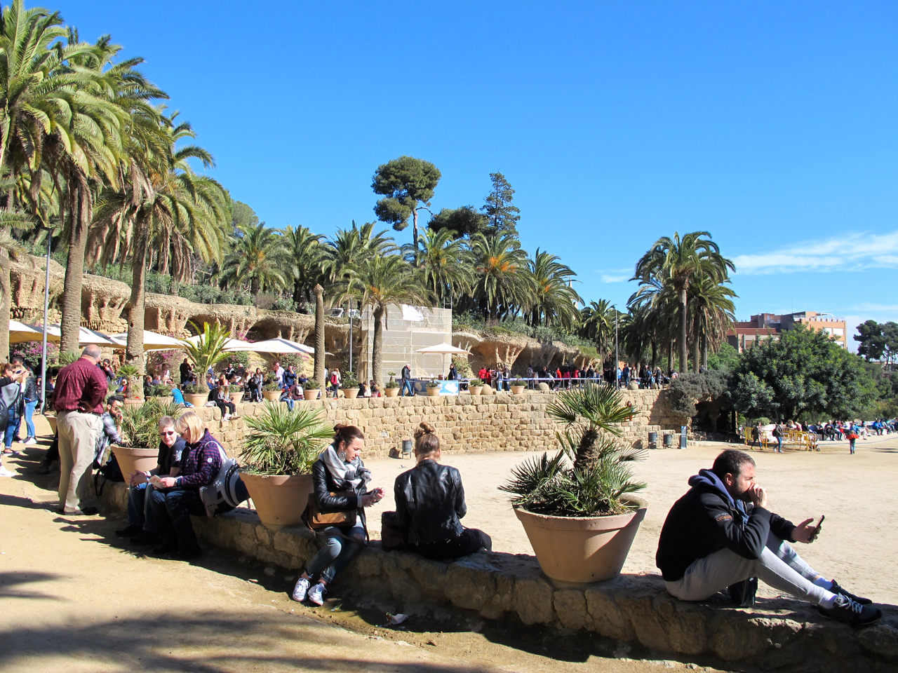 Der Park Güell ist voll mit Menschen die die Sonne und den schönen Ausblick auf Barcelonas City geniessen möchten.
